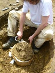 Removing skull embedded in soil to be sent for analysis.